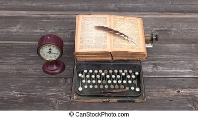 ancient typewriter and old book on wooden background. Wind...
