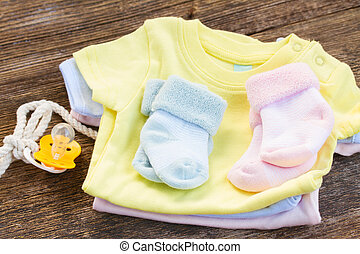 baby clothes - pile newborn baby clothes with pacifier on...