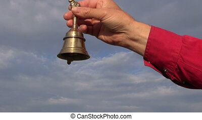 beautiful brass bell sound in hands and sky background