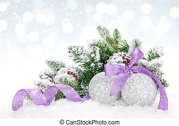 Christmas baubles and purple ribbon over snow bokeh...