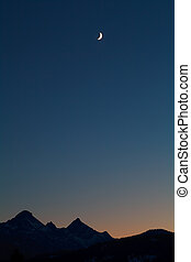 moon and mountain silhouettes over dark sky, Alps