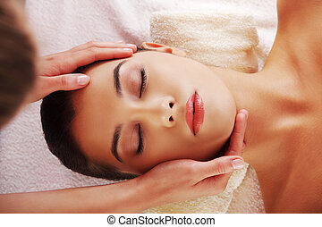 Young woman face massage in spa