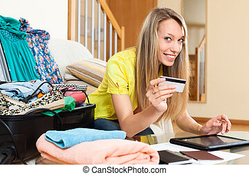 Smiling woman using credit card for reserving plane ticket -...