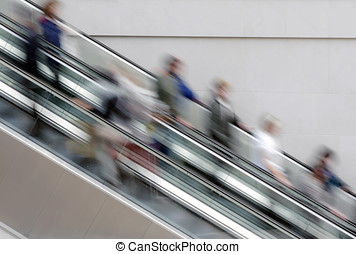 People on escalator - People travelling on escalator taking...