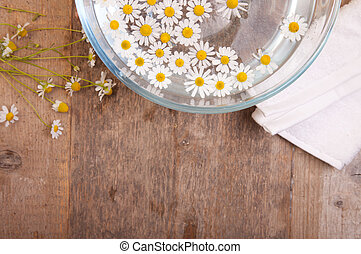 camomiles in bowl of water and next to it white towel