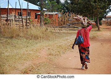 An African woman while carrying the wood for the fire -...