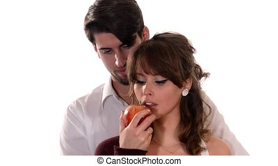 young lovers eating a red apple - Young couple over white...