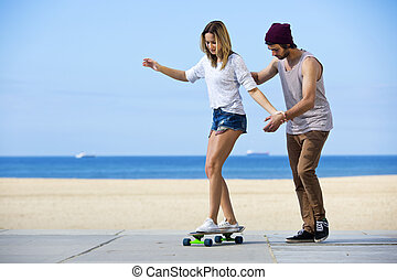 Skateboarding workshop - Young man gives his girlfriend her...
