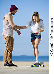 Skateboard lesson - Young woman, learning how to ride a...