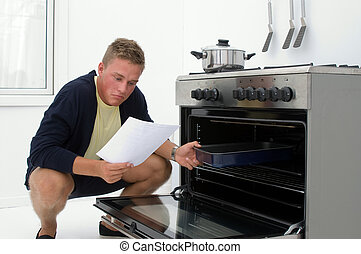 young man clueless in kitchen reading from recipe
