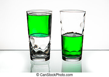 Two glasses, both half-full of green liquid. - Half empty or...