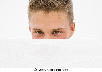 young man hiding himself behind a white towel