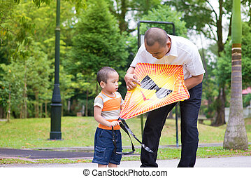 Flying kite - Father teaching son to fly a kite at outdoor...