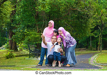 Asian family - Happy Southeast Asian family outdoor...