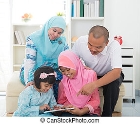 Southeast Asian family surfing internet at home. Muslim...