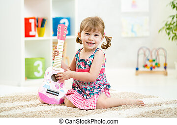 little girl with guitar toy gift siiting on floor