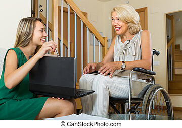 Social worker and handicapped woman with laptop - Female...