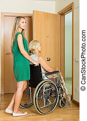 Girl helping handicapped woman - Smiling girl helping...