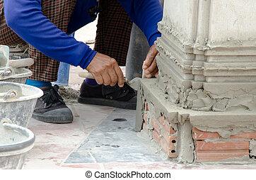 plastering - Workers plastering on red brick pillars.