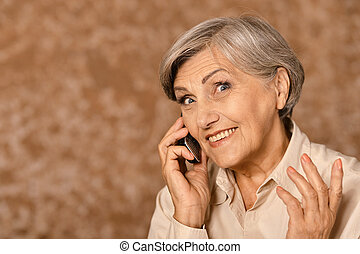 Elderly woman talking on mobile phone on beige background