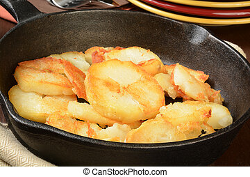Home fried potatoes in a cast iron skilled with serving...