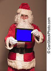 Santa Claus showing you a computer tablet pad, on studion...