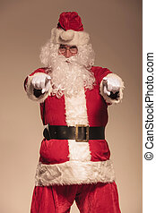Portrait of Santa Claus pointing at the camera, on studion...