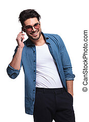 man holding his hand in pocket while talking on phone