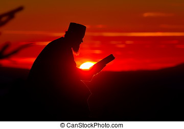 silhouette of priest reading in the sunset light, Romania, Ceahl