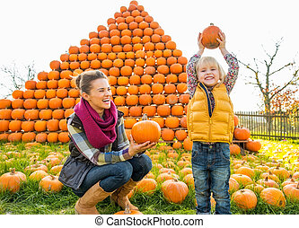 Portrait of happy mother and child pumpkin in front of...