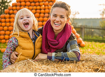 Portrait of smiling mother and child near haystack
