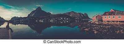 Woman sitting on a pier in Reine village, Norway
