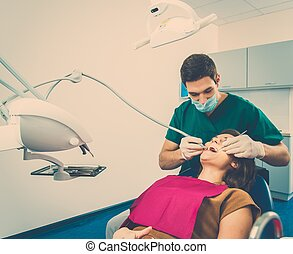 Young woman and man doctor at dentist's surgery