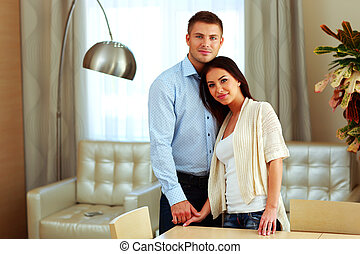 Young beautiful couple standing at home