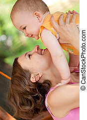 Mother holds her baby aloft - Young mother is holding her...