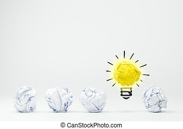 Light bulb with crumpled paper balls on white background