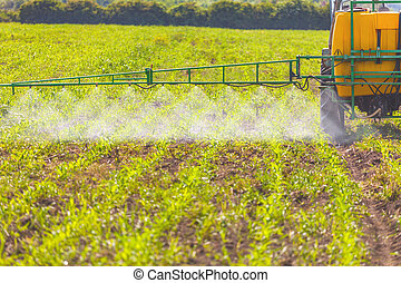 Spreading herbicide - A tractor field sprayer spreading...