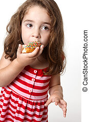 Pretty little girl eating a doughnut - Little girl in a...