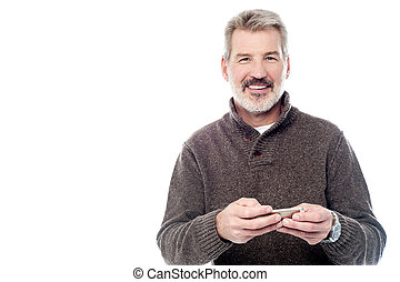 Smiling mature man with mobile phone - Confident aged man...