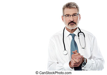 Senior male doctor keeping hands clasped - Mature male...