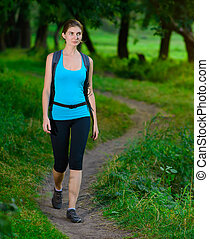 Young Beautiful Woman Hiking in the Green Summer Forest