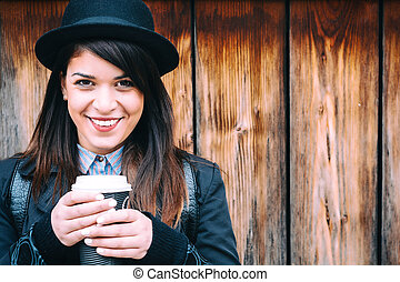 Coffee break - Beautiful young lady smiling while enjoying...