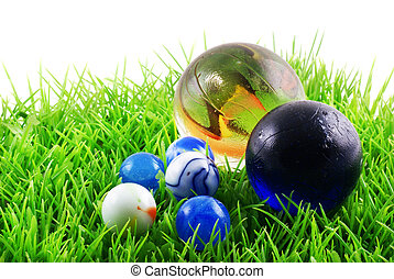 Marbles. - Marbles on grass, isolated on a white background.