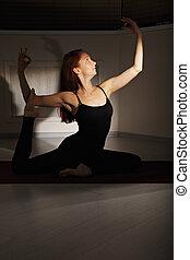 Redhead exercising hatha yoga in a dark gym