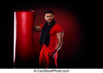 young man standing by boxing bag in studio - young handsome...
