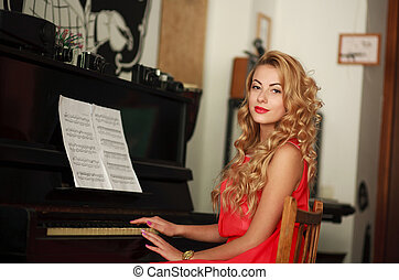 Young woman sitting at the piano - Beautiful young woman...
