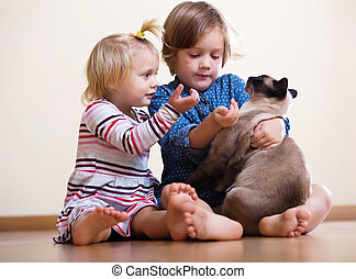 Two happy little girls  with cat