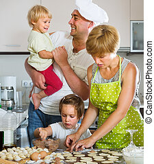 Happy parents with children cooking meat dumplings at home...