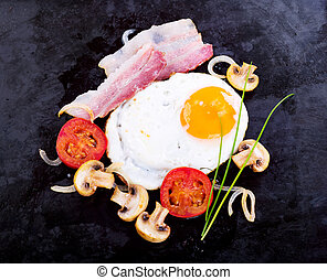fried egg with bacon, mushrooms and vegetables
