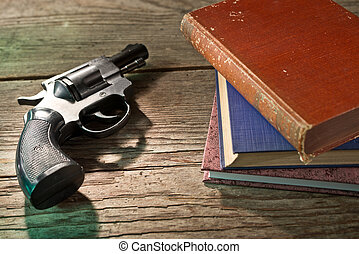 books and handgun - a gun with books on the wooden desk